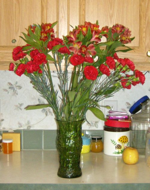red carnations and alstroemerias brighten the kitchen counter