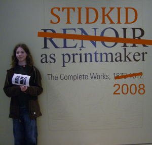 a stidkid in front of the sign announcing the Renoir print exhibit