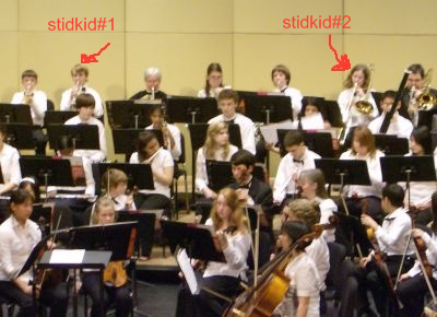 The boys sit in the back row, the trumpeter on the left, the trombone on the right