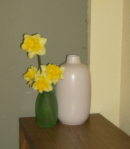 Four yellow daffodils in a green vase, next to a tall pink vase.