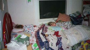 the children asleep on a bed piled high with all their blankets and pillows