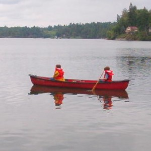 two boys paddling red canoe